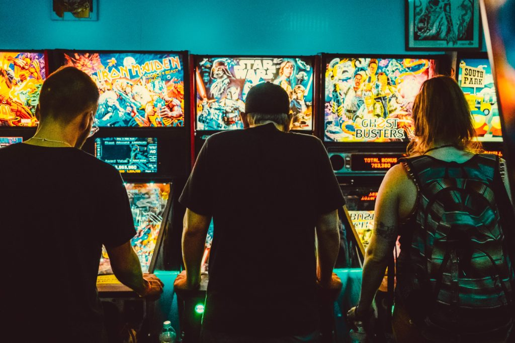 people playing classic pinball machines